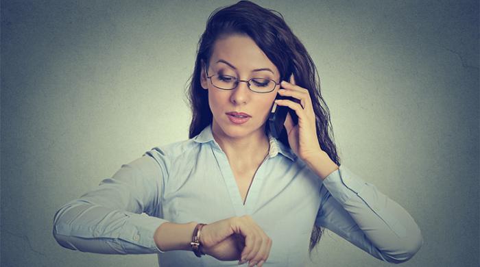 Donna che lavora al cellulare e controlla l'orario di timbratura