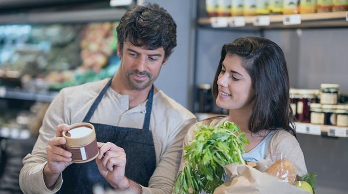 Negoziante spiega l'etichetta posta su un barattolo ad una cliente