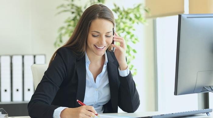 Donna al lavoro utilizzando servizio di conference call aziendale