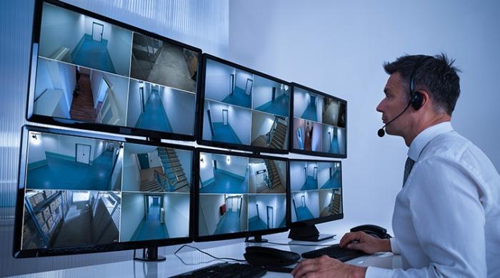 uomo in una sala di monitor che controlla e verifica immagini registrate con videosorveglianza