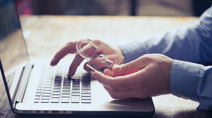 Persona usando il pc tenendo in mano lucchetto per salvaguardare i dati sensibili