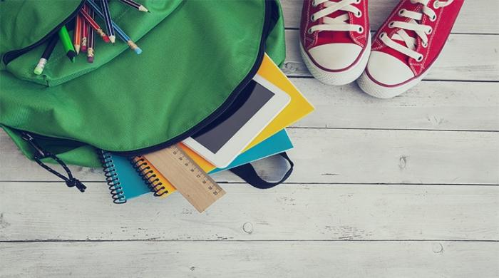 scarpe da bambino e materiale di scuola per terra
